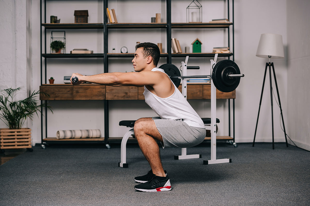 Mann macht Kniebeugen im Home Gym mit Kurzhanteln